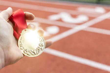 Male hand holding a gold medal in front of a running track.