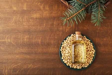 Cedar oil in glass bottle, pine nuts, brunches on a wooden broun background. Top view with copy space
