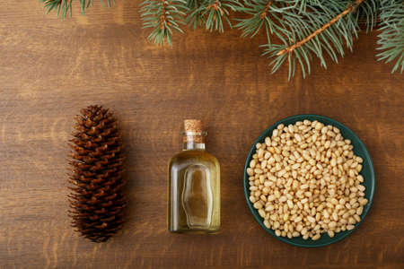 Cedar products: cedar oil in glass bottle, pine nuts, cone, brunches on a wooden broun background. Top view