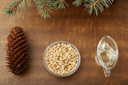Ingredients for pesto: olive oil, pine nuts, cones, brunches on a wooden broun background Imagens