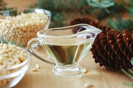 Cedar products: cedar oil, pine nuts, cones, brunches on a wooden broun background