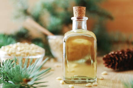 Cedar products: cedar oil in glass bottle, pine nuts, cones, brunches on a wooden broun background