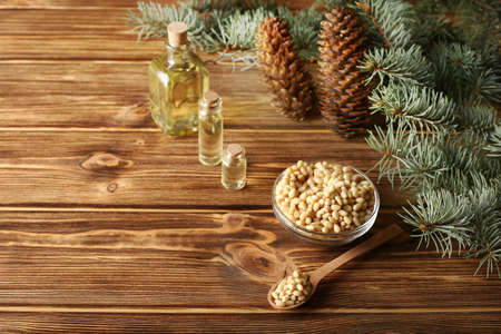 Cedar pine nuts in glass bowl with cones, oil, spoon, cedar brunch on wooden background with copy space