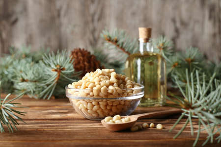 Cedar pine nuts in glass bowl with cones, oil, spoon, cedar brunch on wooden background