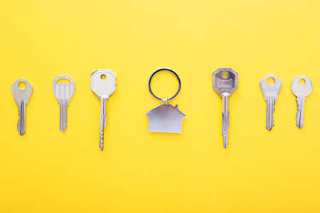 Keys and trinket in shape of house in the center on color background, top view