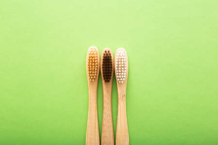 Dental care with eco friendly bamboo toothbrush on green background top view. Zero waste and plastic free concept