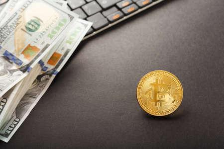 Close up shot gold Bitcoin on dollar banknote over computer on black background Banco de Imagens