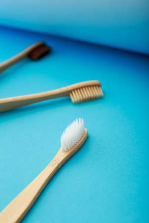 Dental care with eco friendly bamboo toothbrush on blue background. Zero waste and plastic free concept Stock Photo