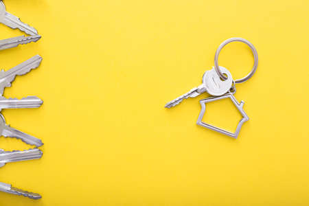 House keys with trinket on color background, top view with copy space