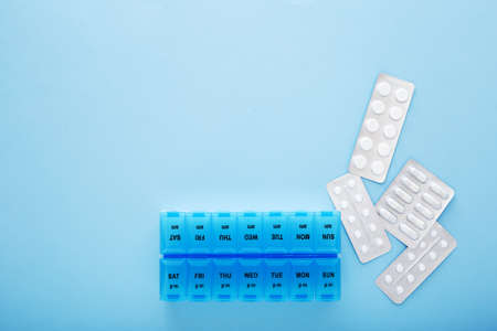 blue plastic 14 day pill box with pills on blue background. Top view