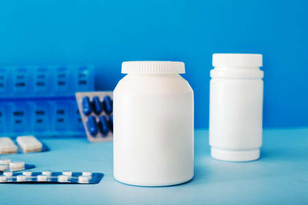 White medical pills and tablets spilling out of a bottle. Mock up bottles with copy space