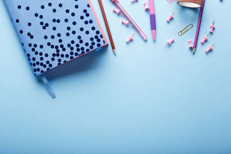 Notebook and school supplies on blue background. Back to school. Flat lay