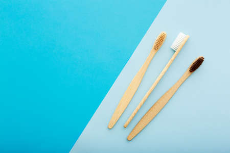 Dental care with eco friendly bamboo toothbrush on blue background top view. Zero waste and plastic free concept