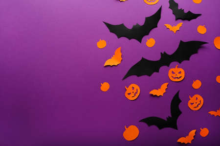 Halloween background with pumpkins, spider, black, orange paper bats flying over purple background, . Copy space. Halloween and decoration concept