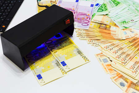 Money fake testing - euro banknotes authentication check in UV Currency Detector lights. Counterfeiting banknotes, checking at the bank by cashier, bank operator. Financial, banking concept. Фото со стока
