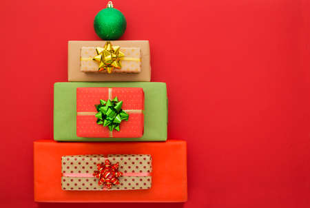 Christmas composition. Christmas gift boxes laid out in the shape of a Christmas tree on red background. Flat lay, top view, copy space Stock Photo