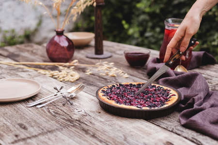 Female hands are cutting berry pie on wooden table in rustic style . Homemade cheesecake on the outdoor 스톡 콘텐츠