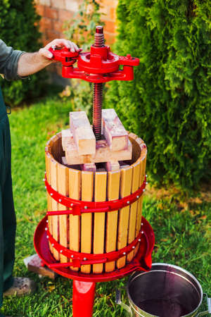 Wooden Winepress machine with red details. Crusher on the grass outdoors. Grape harvest. Special equipment for the production of wine, winemaking. Concept of small craft business, home made wine. Autumn winery.