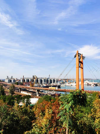 Highway bridge, Railroad on seaport, harbor background with Granary elevators, yachts, ships, floating cargo cranes in the port of Odessa in autumn. Logistic export import transport industry concept.