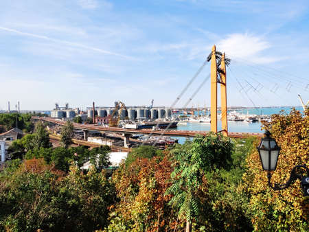 Highway bridge, Railroad on seaport, harbor background with Granary elevators, yachts, ships, floating cargo cranes in the port of Odessa in autumn. Logistic export import transport industry concept