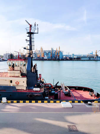Tugboat assist on a pier in the harbor, cargo sea port over the sea, Floating cargo crane, Granary elevators, harbor, boats and cranes. Industrial scenery of the sea cargo port