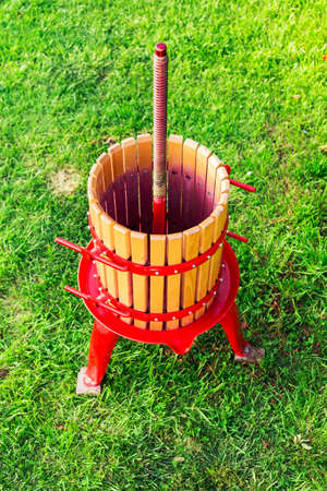 Wooden Winepress machine with red details, Crusher on the grass outdoors. Grape harvest. Special equipment for the production of wine, winemaking. Concept of small craft business, home made wine. Autumn winery Reklamní fotografie