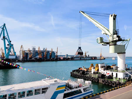Floating cargo crane with a ladle in the seaport over the sea and Granary elevators, Tugboat assist, boats and cranes. Industrial scenery of the sea cargo port, harbor. Excavator on floating platform