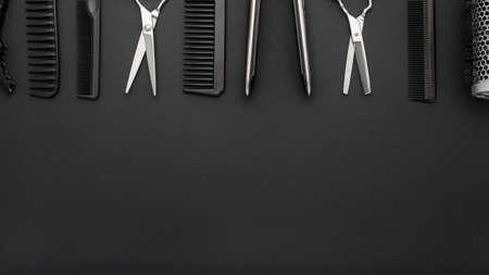 Flache Zusammensetzung mit Friseurwerkzeugen: Schere, Kämme, Haareisen auf schwarzem Hintergrund. Rahmen. Friseurservice. Schönheitssalon-Service. Friseur-Set. Langer Fahnenhintergrund mit Kopienraum