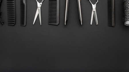 Flat lay composition with Hairdresser tools: scissors, combs, hair iron on black background. Frame. Hairdresser service. Beauty salon service. Hairdresser Set. Long banner background with copy space 스톡 콘텐츠