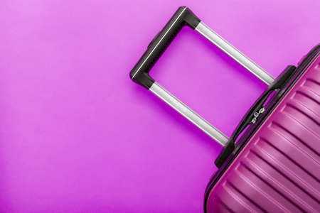 Modern pink suitcase on pink background close up with copy space for text. Minimal style travel concept. Vacation trip. Summer holiday stock photo. 版權商用圖片