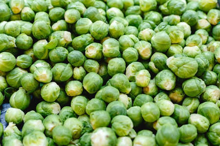 Fresh raw organic uncooked Brussels sprouts vegetables for sale at farmers market. Vegan food and healthy nutrition concept. Top view stock photo Brussels sprouts as food background