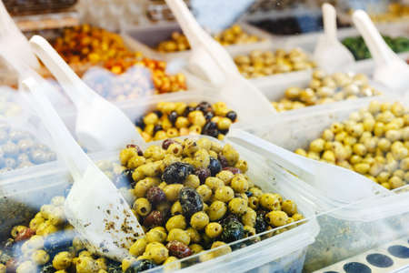 Different Types of olives at market. Mix green, black olives with garlic, pesto sauce, herbs on a counter with a scoops for sale. Stock photo traditional spanish italian food olives 写真素材