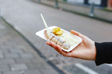 Holland herring fish in female hand outside. Traditional Dutch street food, herring fish. Stock photo street food, herring fish with onions and pickles