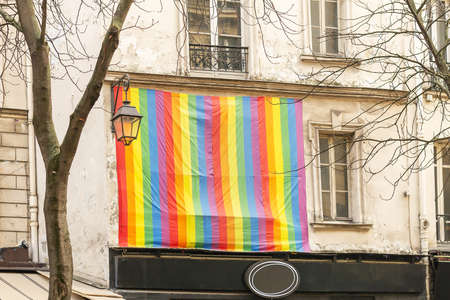 Facade with gay pride flag instead of a window Paris, France. Rainbow flag of the LGBT community as a symbol of love, freedom, equality, rights concepts