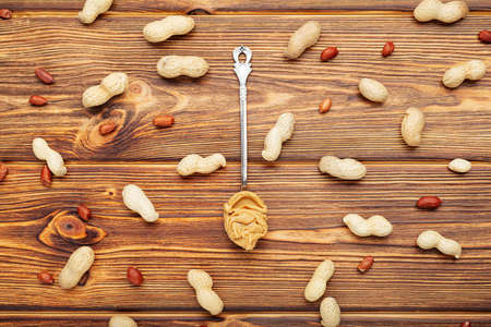 Vintage spoon with creamy peanut butter on a brown wooden table. Near the peanut butter lies peanuts in the shell and peeled peanuts.Flat lay of peanut paste for cooking breakfast. Vegan food concept