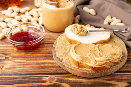 Peanut butter in spoon near creamy peanut paste in open glass jar, slice of peanut butter bread, toast, jam. Peanuts in peel scattered on brown wooden table with copy space for cooking breakfast.