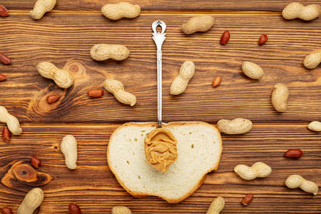 Vintage spoon with creamy peanut butter on a toast, slice of bread. Peanuts in the shell and peeled peanuts on brown wooden table. Flat lay of peanut paste for cooking breakfast. Vegan food concept 写真素材