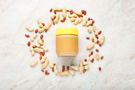Creamy peanut paste in glass jar with yellow cap and peanuts in the shell and peeled peanuts. Creamy peanut paste flat lay with place for text on white marble background for cooking breakfast 写真素材