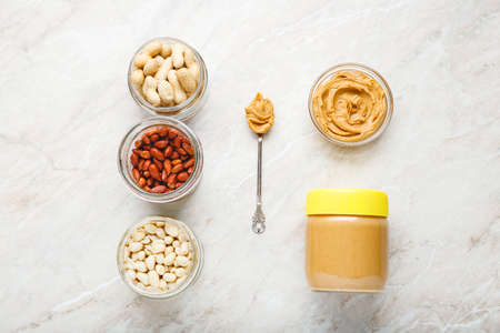 Ingredients for cooking of peanut butter. Peeled and unpeeled peanuts, peanut butter in jar and peanut butter in a spoon on a white marble background.Flat lay of cooking natural healthy food concept. 写真素材