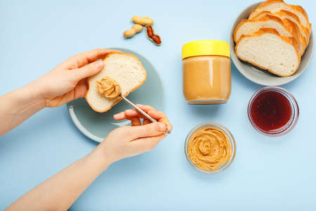 Top view,flat lay process of cooking breakfast, spreading bread, toast with peanut butter, creamy peanut paste by female hands on blue colored background.Served by peanut butter, peanuts in shell,jam