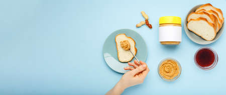 Cooking process breakfast, spreading bread, toast with peanut butter,peanut paste by female hands on blue colored background.Served by peanut butter,peanuts in shell,jam.Top view,flat lay,long banner.