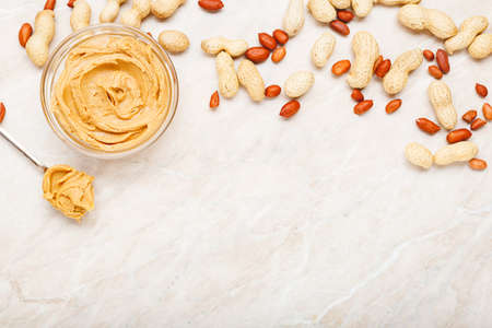 Peanut butter in glass plate with peanuts in shell, peeled peanuts, vintage spoon with peanut butter. Creamy peanut paste flat lay with place for text on white marble background for cooking breakfast