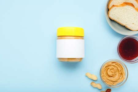 Mock up for peanut butter, creamy peanut paste.Top view,flat lay,long banner. Process of cooking breakfast on blue colored background. Served by peanut butter,peanuts in shell, jam