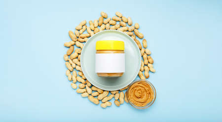 Creamy peanut paste in glass jar with yellow cap with mock up and peanut butter in a glass plate. Peanuts in the peel scattered on blue background. Minimalistic food flat lay on color background