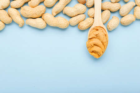 Frame made of nuts peanuts in shell and wooden spoon with creamy peanut butter with copy space on blue colored background. Flat lay with place for text for peanut butter, peanut paste. Vegan food conc
