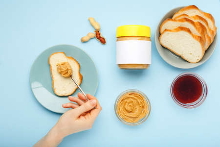 Mock up for peanut butter, creamy peanut paste.Top view,flat lay process of cooking breakfast, spreading bread, toast with peanut butter,creamy peanut paste by female hands on blue colored background