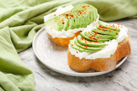 Two avocado toasts on gray plate, avocado sandwich. Fresh avocado sliced on toast of wheat bread, cream cheese.Avocado sprinkled with chili spices on gray concrete background with copy space,top view. Stock Photo