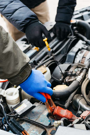 Two Car mechanic engineers checking, fixing the car, making maintenance comprehensive auto check. Auto mechanic charging car battery with electricity using jumper cables. Car repair service.