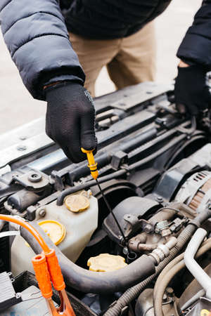 Man in black gloves checking the oil level in a car outdoors in winter. Car mechanic engineer working in car repair service. Male hands fixing a car, checking the oil level