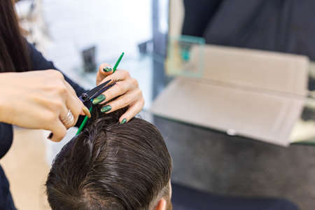 Female Hairdresser hands doing haircut for male client using professional hairdresser tools scissors, brush on hairdresser work space. Hairdresser service. Beauty salon hair cut service. Close up.